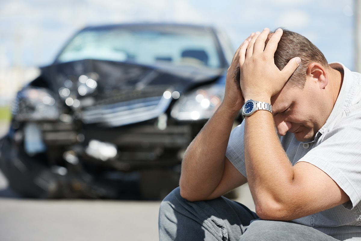 Upset man in front of a car accident