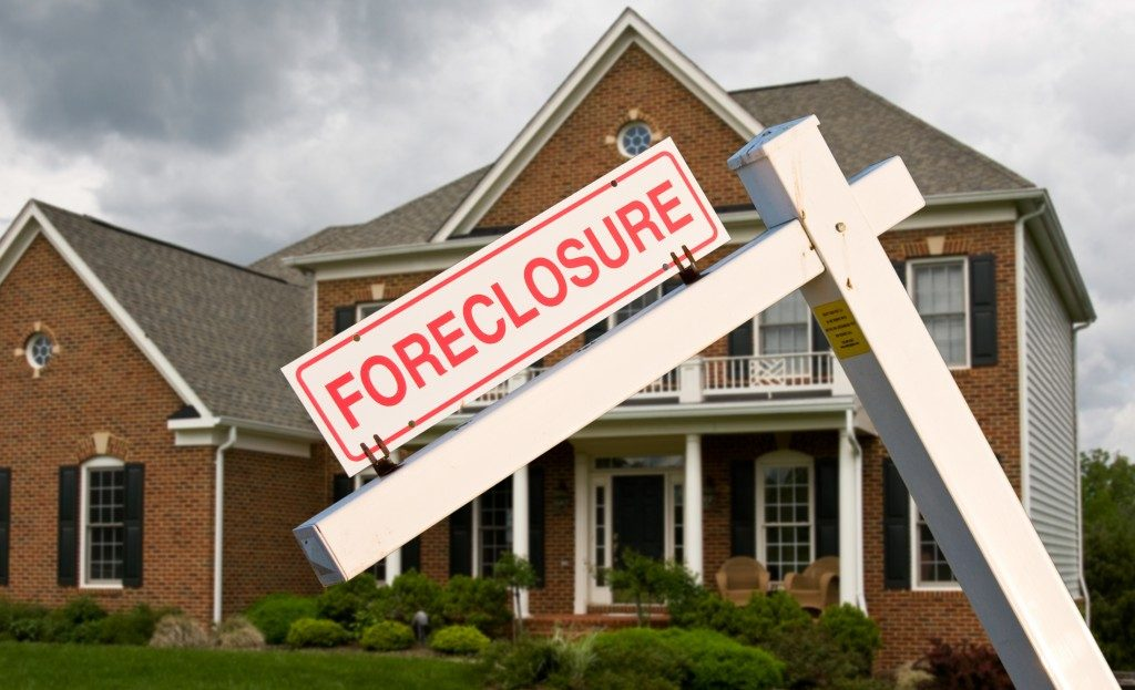 Leaning foreclosure sign in front of house
