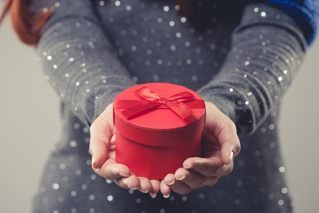 gift box cradled in the cupped hands of a woman