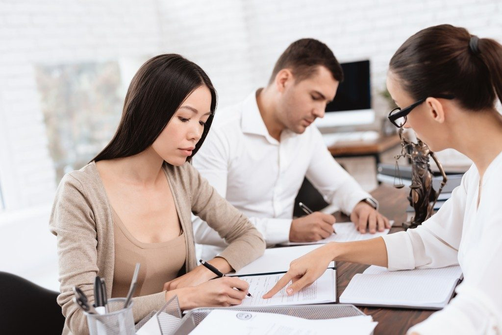 Divorce lawyer instructing client where to sign