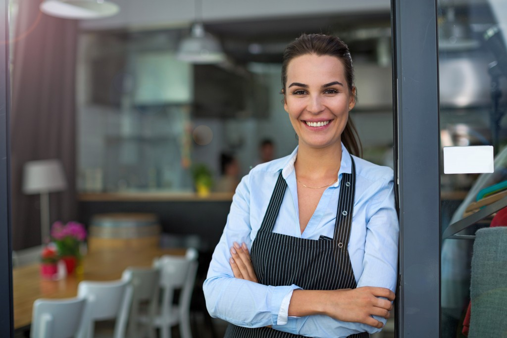 Restaurant owner posing with her arms crossed