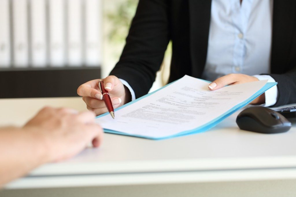 Woman handing paper and pen