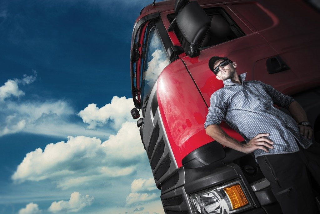 Man posing behind his red truck