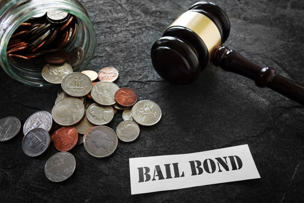 coins gavel and paper with bail bond written