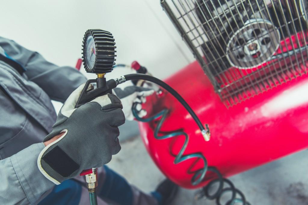 Man adjusting pressure of air compressor