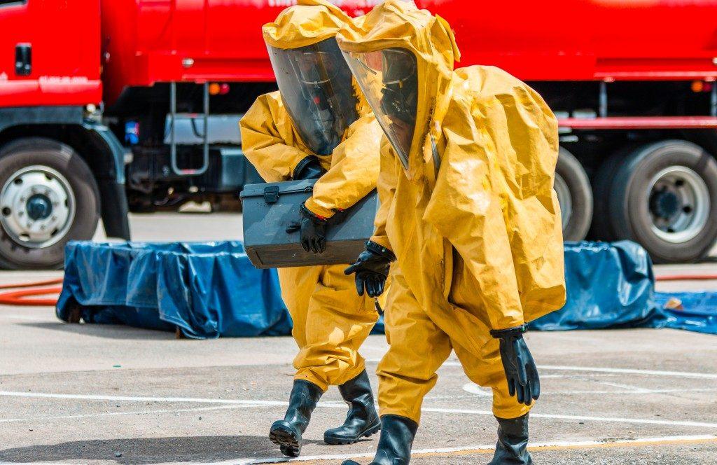men carrying hazardous waste