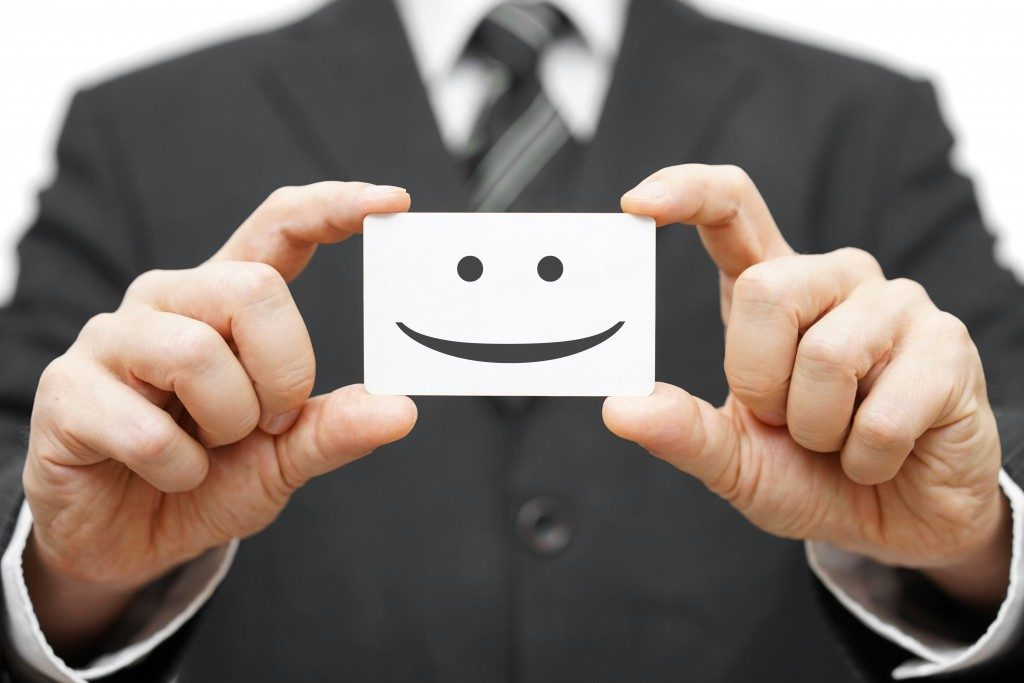 Businessman holding a card with smiley