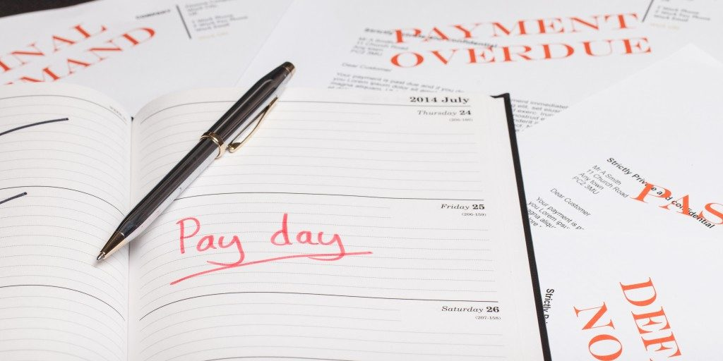 Writing down schedule for payment in personal journal