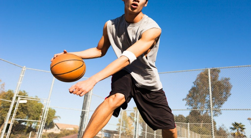 Man playing basketball outdoors