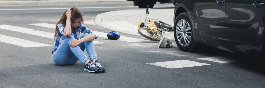 woman sitting on the road after a car accident