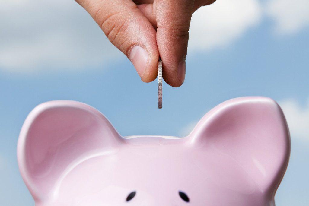 hand putting a coin into a piggy bank