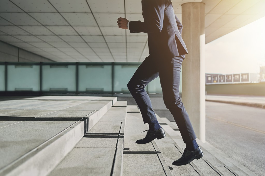 Man in business attire going up the stairs