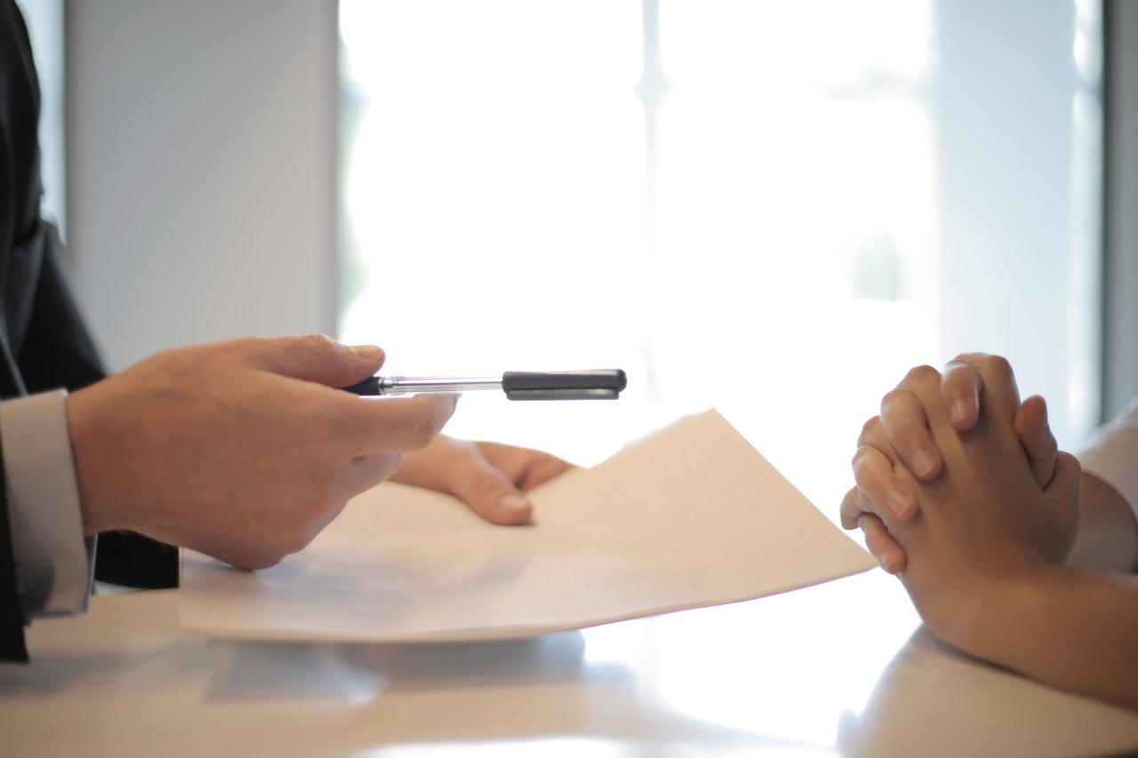 handing over pen and paper