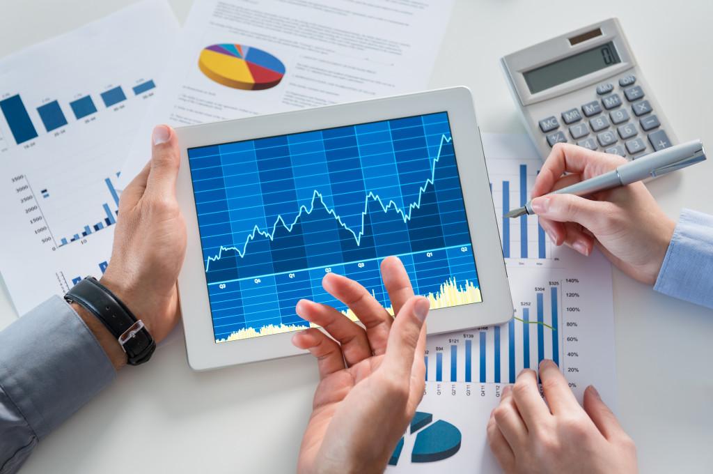 рука, держащая компьютерный планшет и ручку для управления финансами